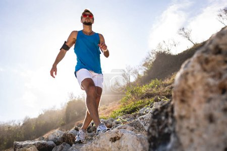 bottom view of sportsman walking on rocks on mountain with sunlight