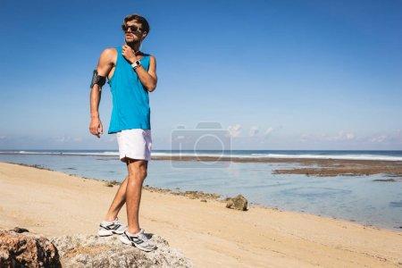 Photo pour Musique écoute sportif avec smartphone le brassard en se tenant debout sur la plage, Bali, Indonésie - image libre de droit