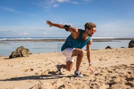 Photo for Athletic handsome man doing lunges during workout on seashore - Royalty Free Image
