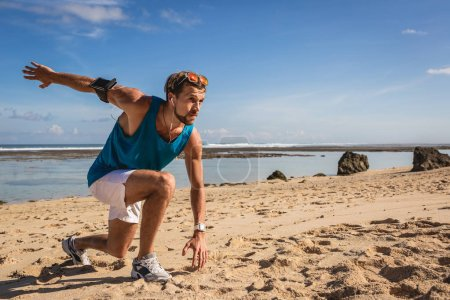 athletic man with armband doing lunges during workout on seashore