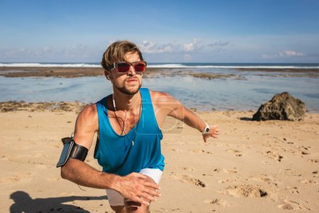 sportsman with smartphone armband working out on beach near sea