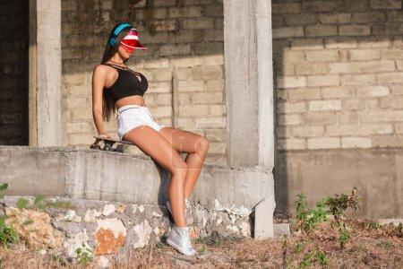 beautiful woman in headphones sitting on skateboard near concrete building under construction
