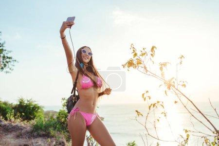 Photo pour Jolie fille en casque et en bikini rose prenant selfie smartphone sur la plage pendant le coucher du soleil - image libre de droit