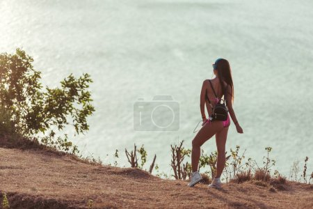 back view of girl in headphones, pink bikini and bag looking at sea from beach