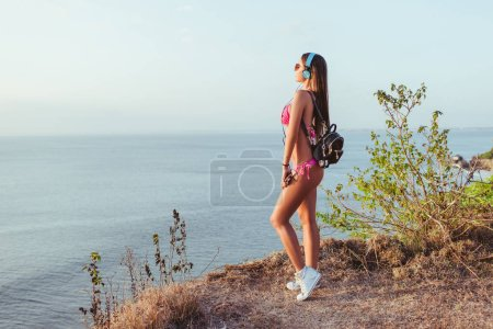 side view of attractive girl in pink bikini and headphones looking at ocean at beach