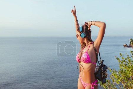 smiling beautiful woman in headphones and pink bikini dancing at beach