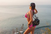 side view of attractive girl in headphones and pink bikini posing at beach