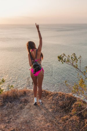 back view of girl in headphones and pink bikini dancing at beach with raised hand