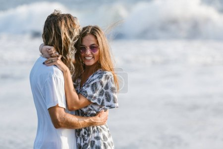 side view of couple hugging on ocean beach in bali, indonesia