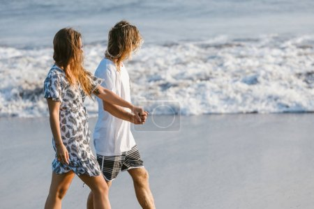 side view of couple holding hands and walking on beach in bali, indonesia