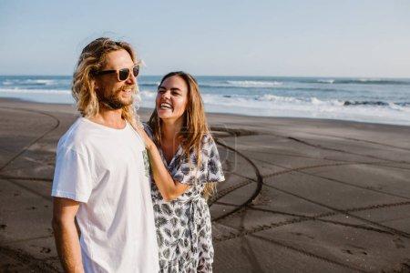 laughing couple hugging on coastline in bali, indonesia