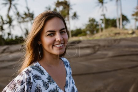 Photo for Portrait of smiling attractive girl looking at camera on beach in bali, indonesia - Royalty Free Image