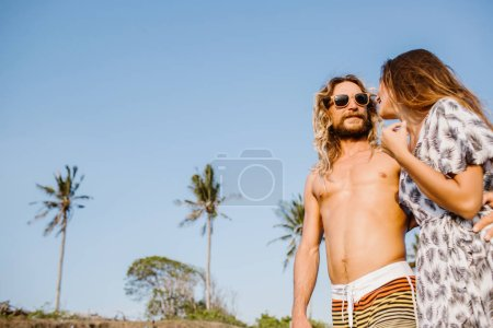 low angle view of couple hugging and walking on beach in bali, indonesia
