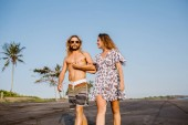 couple holding hands and walking on beach in bali, indonesia
