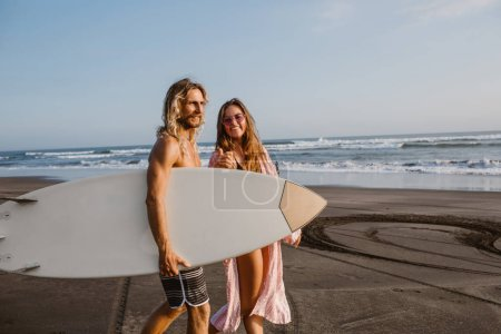 happy couple walking together on beach with surfing board in bali, indonesia