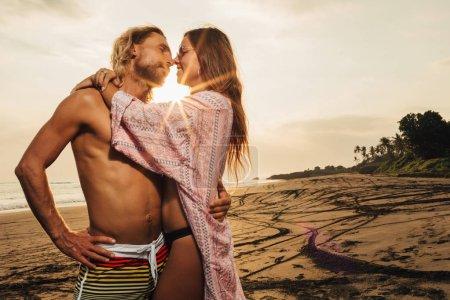Photo pour Couple hétérosexuel câlins sur la plage pendant le coucher du soleil à bali, indonesia - image libre de droit