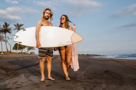couple standing with surfboard on beach in bali, indonesia