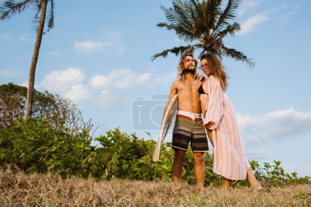 smiling girlfriend hugging boyfriend with surfboard near palm trees in bali, indonesia