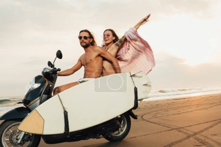 couple riding motorbike with surfboard on beach in bali, indonesia