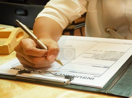 Photo pour La main humaine remplit les informations sur le formulaire de réclamation d'assurance , - image libre de droit