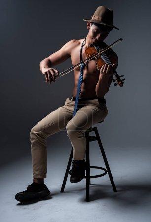 Photo pour Jetez bel homme montrer muscle du corps, assis sur une chaise noire, jouer du violon avec un sentiment heureux, vintage et ton d'art - image libre de droit