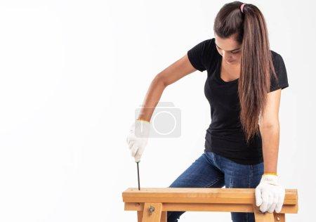 Photo pour La belle femme porte un T-shirt noir et un jean bleu, utilise un tournevis pour réparer une étagère en bois, travaille le bois toute seule - image libre de droit