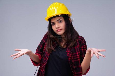 Photo pour La jeune femme ingénieur avec casque de sécurité jaune, regardant droit et lever les mains, avec une attitude indifférente - image libre de droit