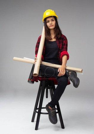 Photo pour La jeune femme ingénieur a mis un casque de sécurité jaune sur sa tête, assise sur une chaise en bois, tenant le plan dans sa main, regardant droit, - image libre de droit