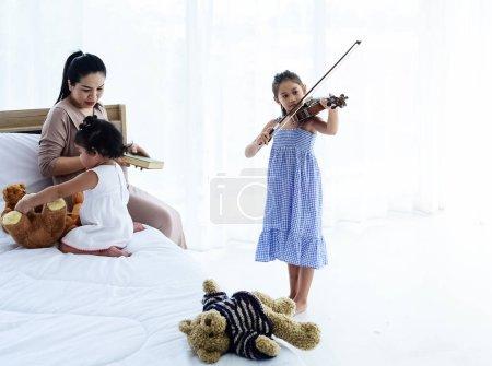 Photo pour Le petit gril jouant du violon, sa mère et sa sœur assises sur le lit, faisant de l'activité ensemble, à la maison, heureux sentiment, lumière floue autour - image libre de droit