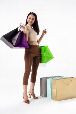 Photo pour La belle femme tenant des sacs à provisions dans la main, twith sourire et sentiment heureux, la dame shopaholic, - image libre de droit
