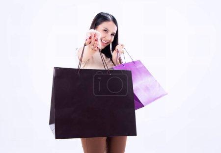 Photo pour Gros plan sac à provisions a été montrant à la main de femme de beauté floue, avec sourire et visage heureux, shopaholic, sur le fond, lumière floue autour - image libre de droit