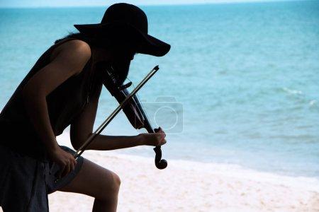 Photo pour La belle femme montrant comment jouer du violon, sur le côté gauche du fond de la plage - image libre de droit