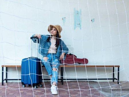 Photo pour La belle femme assise sur une chaise en bois à côté des bagages et de la boîte en ukulélé, se prépare pour voyager, en vacances - image libre de droit