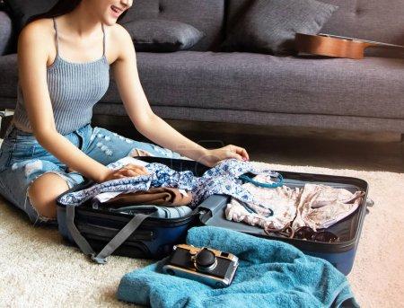 Photo pour La belle femme préparant des draps et des accessoires pour le voyage de vacances, emballant une valise, à la pièce iving , - image libre de droit
