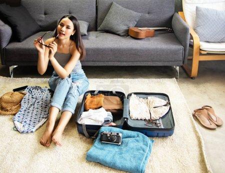 Photo pour La belle femme préparant des draps et des accessoires pour le voyage de vacances, faisant ses valises, dans la salle à manger, avec le sourire et le sentiment heureux - image libre de droit