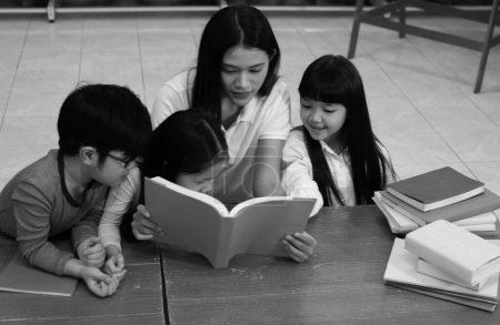 Photo for The beautiful lady reading book with little children with happy feeling,black and white tone - Royalty Free Image