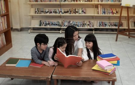 Photo for Three children and beautiful lady reading book together, with happy feeling,blurry light around, - Royalty Free Image