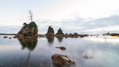 Scenic sunset over panoramic view of Tillamook bay, Oregon. Rock formations stick out the water.