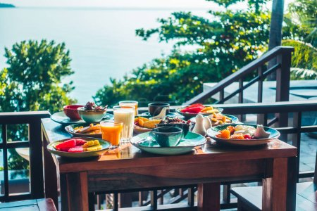 Healthy breakfast set with egg bacon pancakes orange juice milk bread coffee and other on wooden table