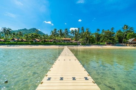 Beautiful tropical beach sea and sand with coconut palm tree on blue sky and white cloud from pier for travel and vacation