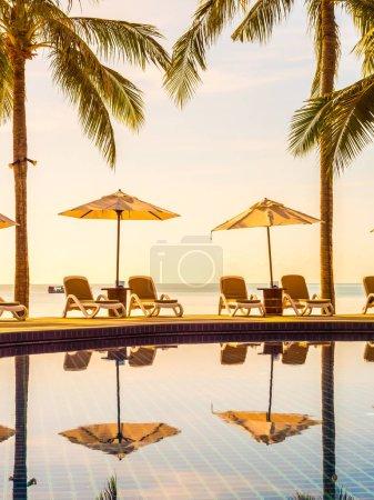 Photo pour Parapluie et chaise autour de la piscine extérieure de luxe dans l'hôtel et la station pour les vacances et les voyages - image libre de droit