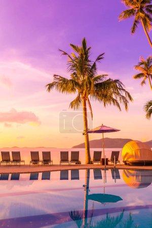 Photo pour Belle vue extérieure avec parasol et chaise autour de la piscine dans un hôtel de luxe et station balnéaire au lever du soleil pour les voyages et les vacances - image libre de droit