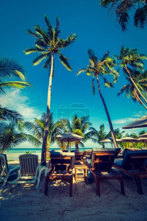 Beautiful outdoor sea and ocean view with umbrella and chair around coconut palm tree for travel and vacation