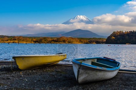 Beautiful landscape of mountain fuji with boat and maple leaf tree around lake in autumn season Yamanashi Japan