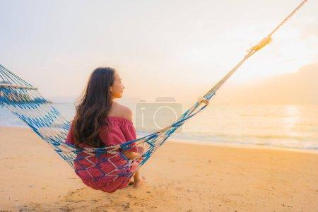 Photo pour Portrait belle jeune femme asiatique assise sur l'hamac avec sourire heureuse plage proche mer et océan pour les loisirs Voyage et vacances au coucher du soleil - image libre de droit
