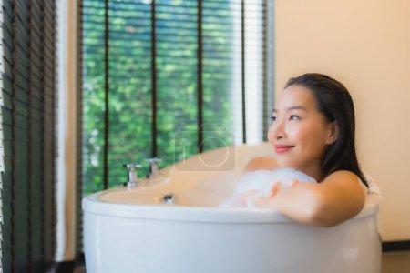 Photo pour Portrait belle jeune femme asiatique sourire heureux relax prendre un bain dans la baignoire de salle de bain intérieur - image libre de droit