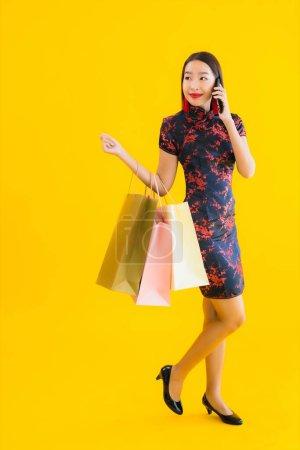 Photo pour Portrait belle jeune femme asiatique porter robe chinoise avec sac à provisions, téléphone portable intelligent, carte de crédit pour le Nouvel An chinois sur fond jaune isolé - image libre de droit