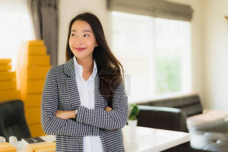 Photo for Portrait beautiful young asian business woman work from home with laptop mobile phone with cardboard box ready for shipping online shopping - Royalty Free Image