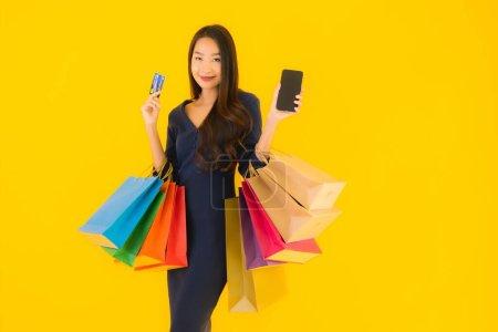 Photo pour Portrait belle jeune femme asiatique avec sac à provisions carte de crédit et téléphone portable intelligent fond isolé jaune - image libre de droit