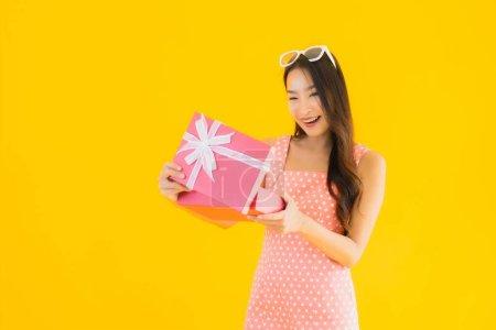 Photo pour Portrait belle jeune femme asiatique avec boîte cadeau rouge sur fond jaune isolé - image libre de droit